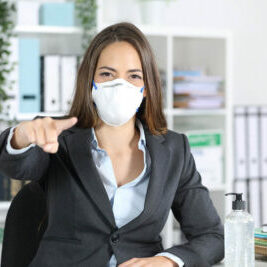 Front view of executive woman with protective mask pointing at you at office